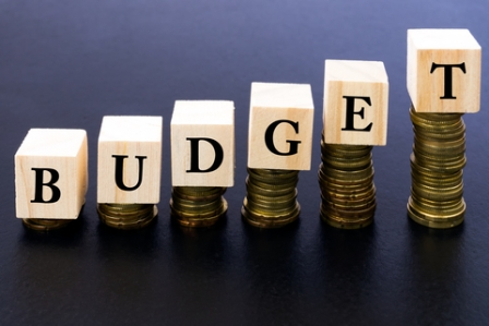 Budget Word on Wood Block on Top of Coins Stack With Black Background.